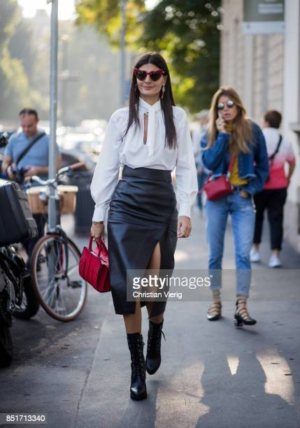 Giovanna Engelbert wearing a black midi skirt with slit, white blouse, black ankle boots, red bag is seen outside Tods during Milan Fashion Week...