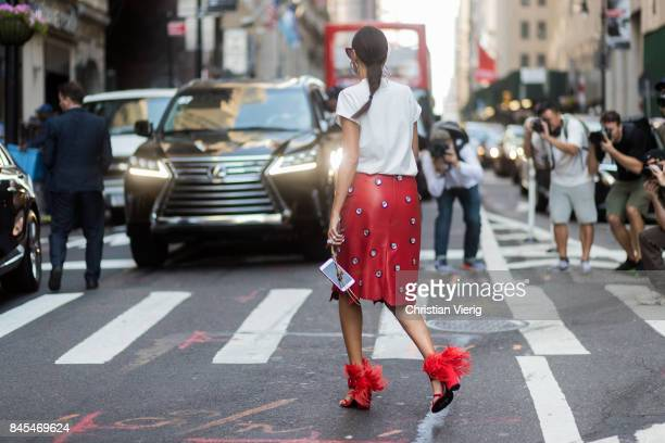 Giovanna Engelbert wearing Bat Gio phone case, a red skirt white tshirt with print red heels seen in the streets of Manhattan outside Victoria...