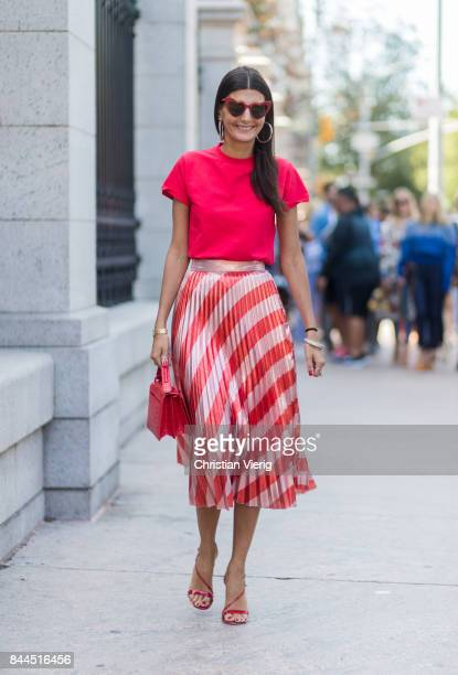 Giovanna Engelbert wearing red tshirt with the print more is glamore red white striped skirt seen in the streets of Manhattan outside Tory Burch...