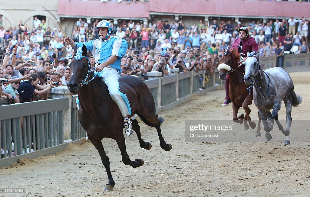 Giovanni Atzeni (L), known as Tittia, rides his horse bareback on his way to winning the Palio dell'Assunta horse-race at Piazza del Campo square on August 16, 2013 in Siena, Italy. The Palio races in Siena, in which riders representing city districts compete, and takes place twice a year in the summer in a tradition that dates back to 1656.