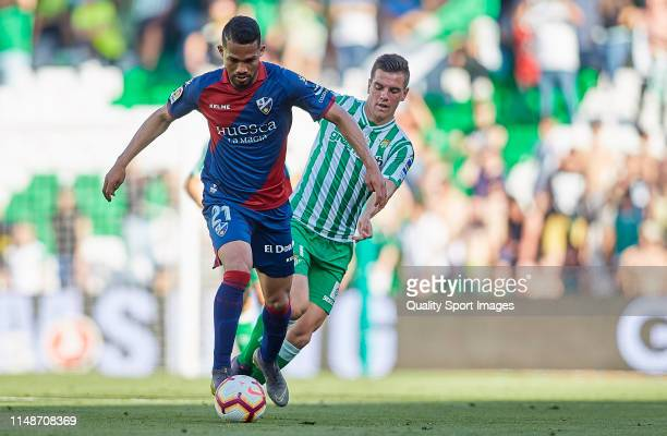Giovanni Lo Celso of Real Betis competes for the ball with Herrera of SD Huesca during the La Liga match between Real Betis Balompie and SD Huesca at...