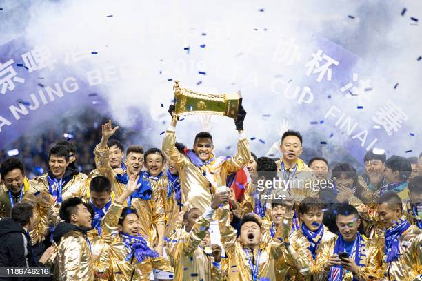 Giovanni Moreno of Shanghai Greenland Shenhua celebrates with the trophy with teammates and staff after winning the 2019 CFA Cup Final Round during...