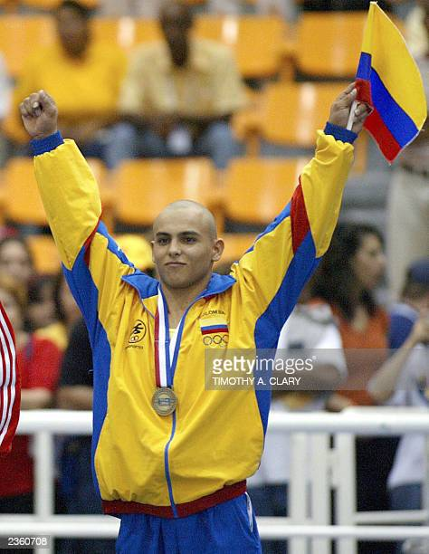 Giovanni Quintero of Colombia holds up his country's flag during the medal ceremony after winning the bronze during the Men's Artistic Gymnastics...