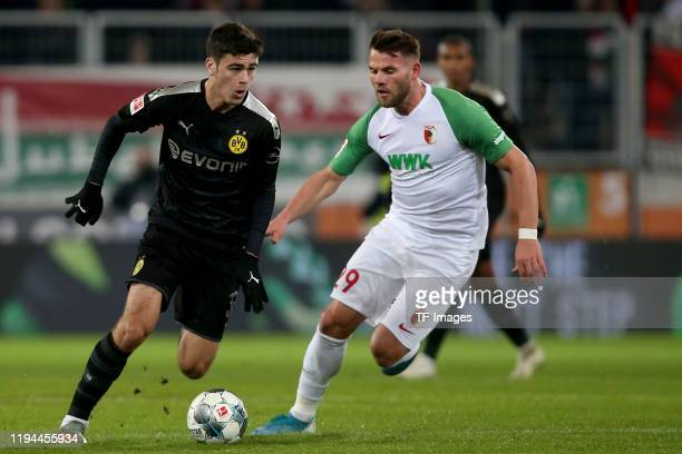 Giovanni Reyna of Borussia Dortmund and Eduard Loewen of FC Augsburg battle for the ball during the Bundesliga match between FC Augsburg and Borussia...