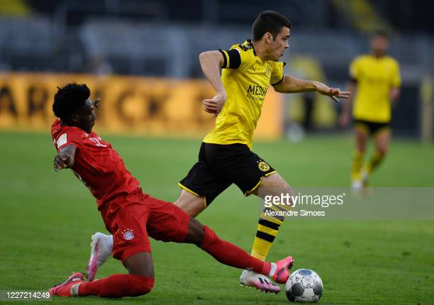 Giovanni Reyna of Borussia Dortmund is challenged by Alphonso Davies of Bayern Muenchen during the Bundesliga match between Borussia Dortmund and FC...