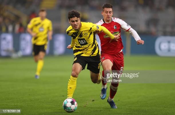 Giovanni Reyna of Borussia Dortmund is challenged by Baptiste Santamaria of Sport-Club Freiburg during the Bundesliga match between Borussia Dortmund...