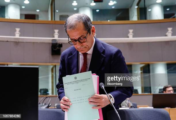 Giovanni Tria Italy's finance minister holds documents ahead of a roundtable discussion during a Eurogroup meeting in Brussels Belgium on Monday Nov...