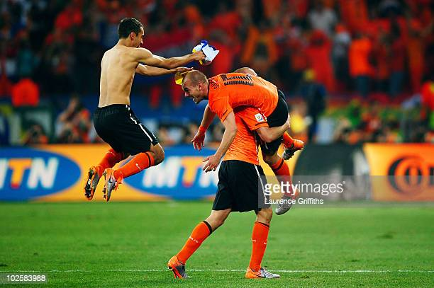 Giovanni Van Bronckhorst and Wesley Sneijder of the Netherlands jump on team mate John Heitinga as they celebrate victory in the 2010 FIFA World Cup...