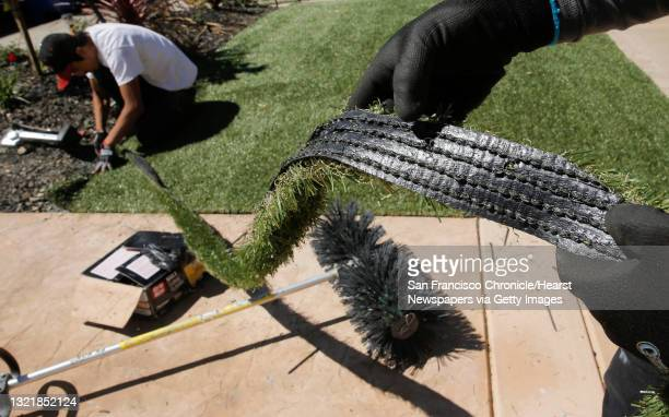 Giovanny Perez with Diamond Greens, displays a piece of the cut material being used as Willie Hernandez, continues the installation of an artificial...