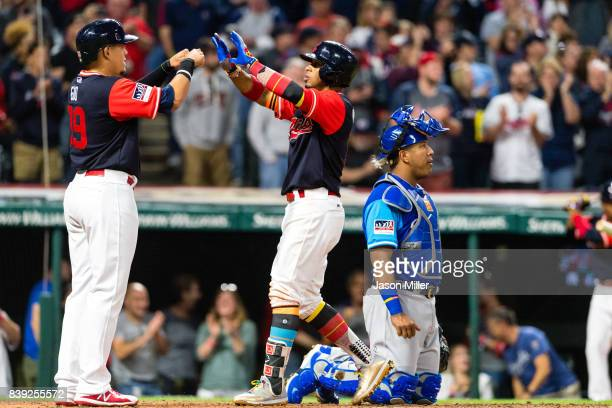 Giovanny Urshela celebrates with Francisco Lindor of the Cleveland Indians after both scored on a Lindor home run as catcher Salvador Perez of the...
