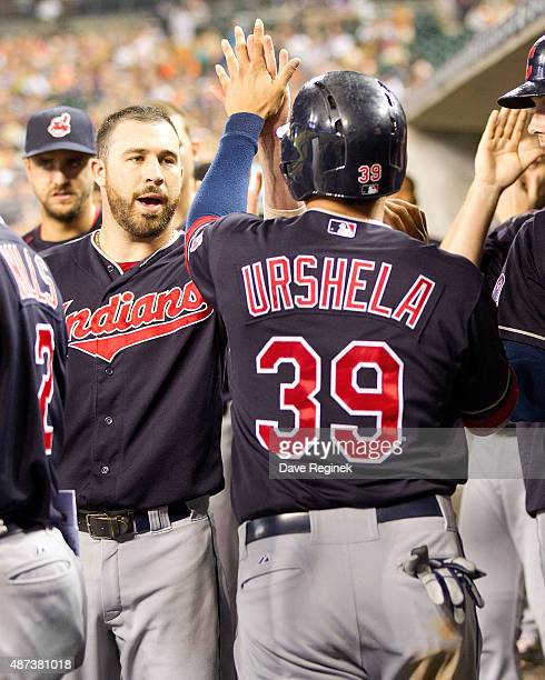 Giovanny Urshela of the Cleveland Indians hifives teammates in the dugout after scoring a run in the fifth inning during a MLB game against the...