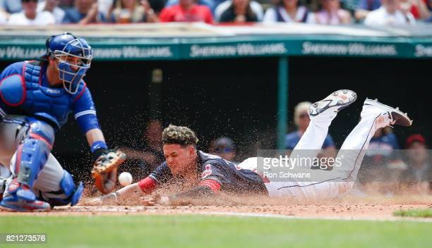 Giovanny Urshela of the Cleveland Indians scores on a single by Francisco Lindor as Miguel Montero of the Toronto Blue Jays takes the throw during...