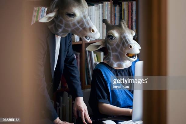 Giraffe heads man and woman working from home