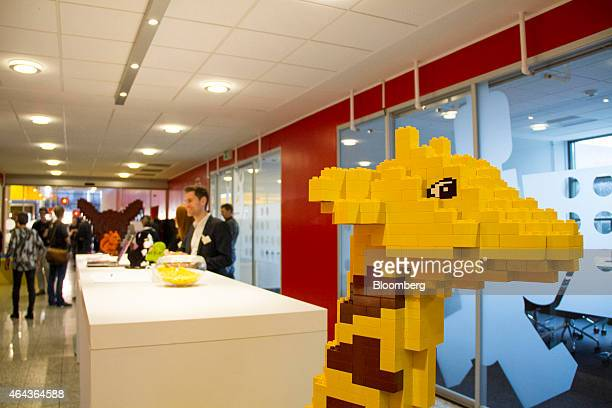 A giraffe made of Lego bricks sits in the reception area as visitors stand beyond at the headquarters of Lego A/S in Billund Denmark on Wednesday Feb...