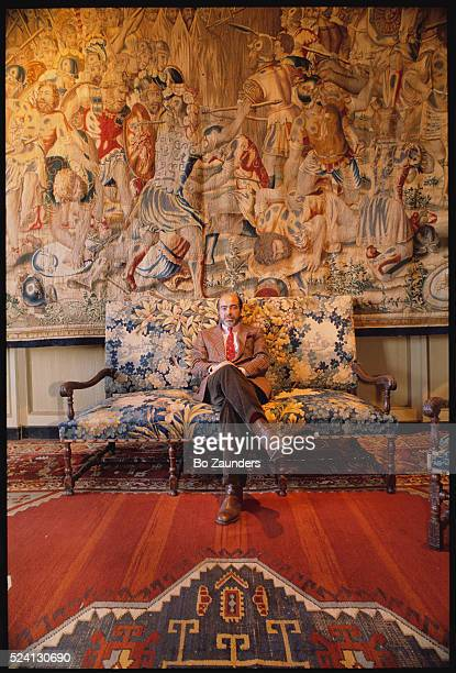 Girard Passerieux owner of Chateau de Paraza sits on antique sofa near elaborate tapestry and rug | Location Minervois France