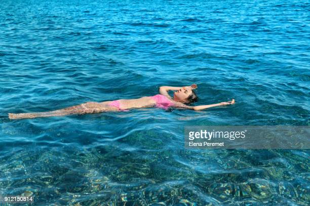 Girl 11-12 years floating on  water in the sea