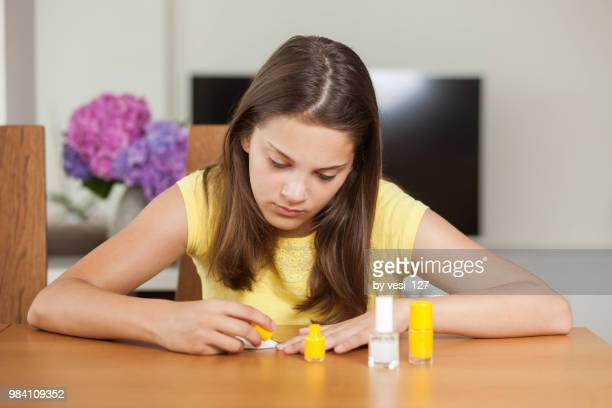 Girl, 12-13 years, painting her finger nails with nail polish