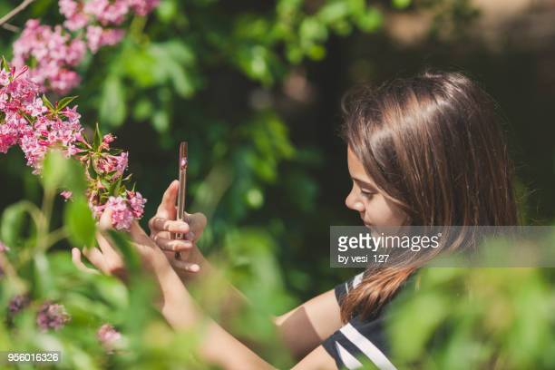 Girl 12-13 years taking pictures with smartphone