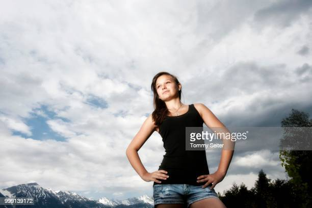 girl, 14 years, looking up thoughtfully, in front of cloudy sky, tyrol, austria - 14 15 years stock pictures, royalty-free photos & images