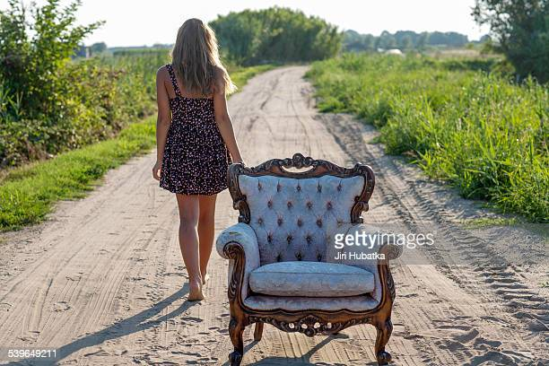 Girl, 14 years, walking along a track, an old armchair in front