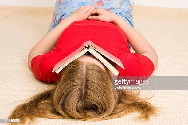 girl, 17 years, lying on the floor covering her face with a book - 16 17 years stock pictures, royalty-free photos & images