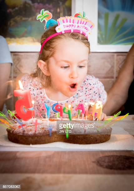 Girl 4-5 years blowing candles at birthday party
