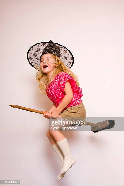 girl, 5 years, with witch's hat flying on broom - witch flying on broom stock photos and pictures