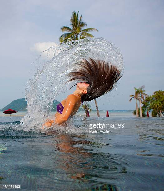 a girl, about 16 years, throwing her hair in the air in a pool of water - vista lateral stock pictures, royalty-free photos & images