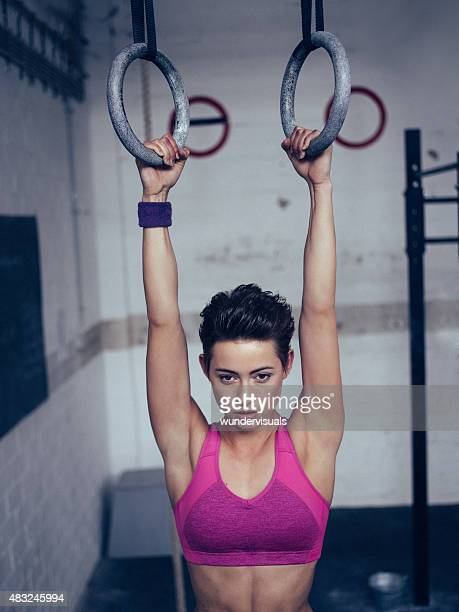 Girl about to do a pull-up on gymnastic rings