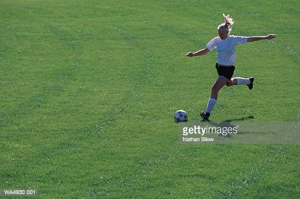 Girl (11-13) about to kick soccer ball, elevated view