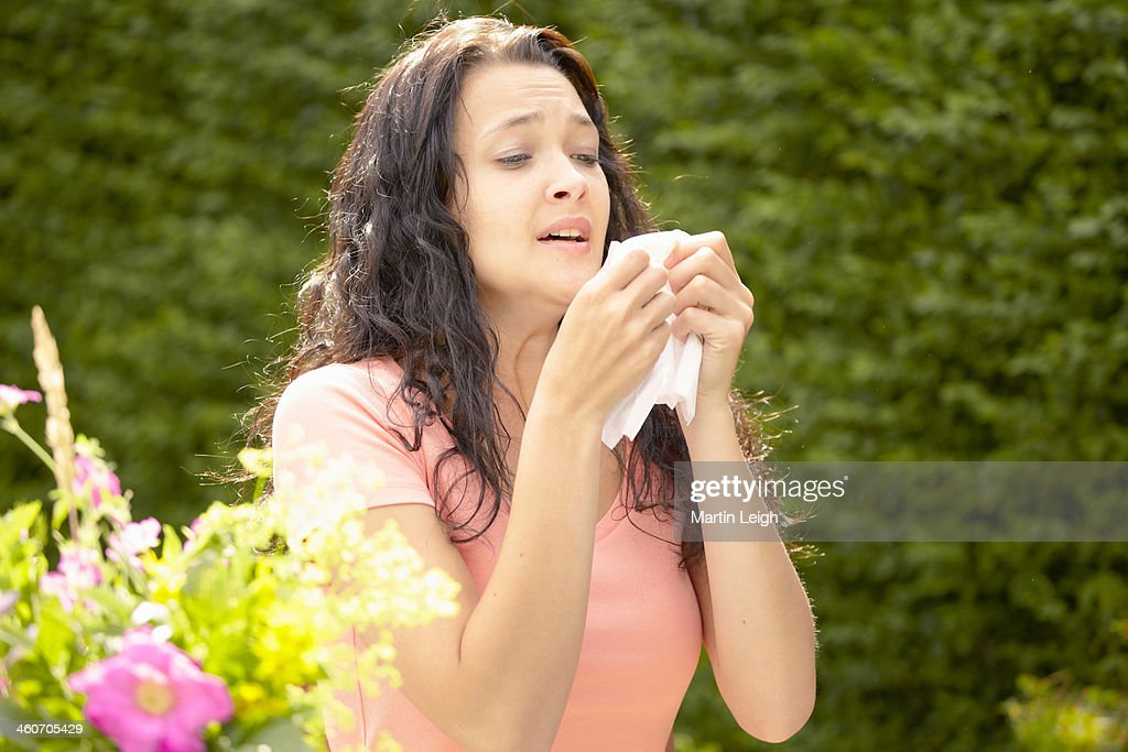 Girl about to sneeze into tissue : Stock Photo