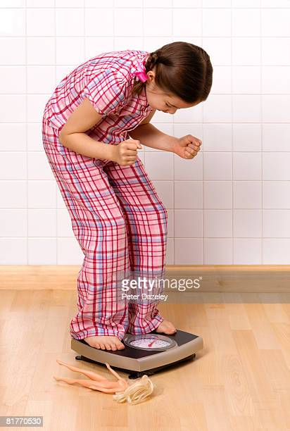 Girl achieving desired weight on bathroom scales.