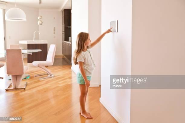 mädchen aktiviert smart-home-sicherheitssystem - izusek stock-fotos und bilder