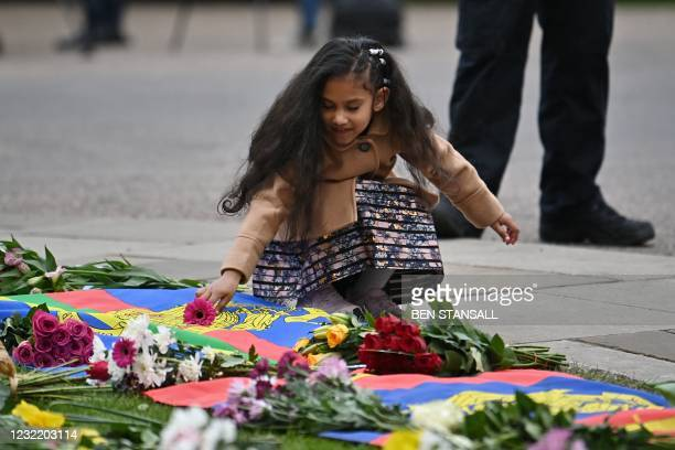 Girl adds a flower to tributes laid outside Windsor Castle, in Windsor, west of London, on April 9 following the announcement of the death of...