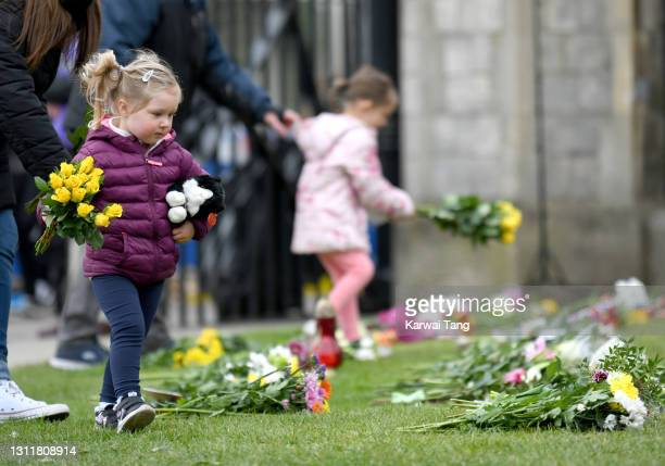 Girl adds her flowers to the floral tributes to Prince Philip, Duke Of Edinburgh who died aged 99, outside Windsor Castle on April 10, 2021 in...