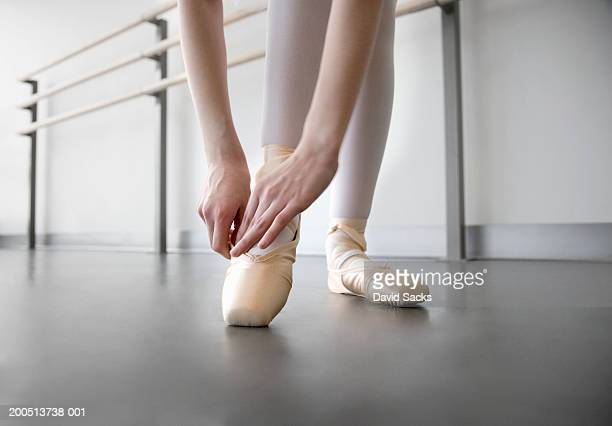 Girl (8-10) adjusting ballet shoe in ballet class, low section