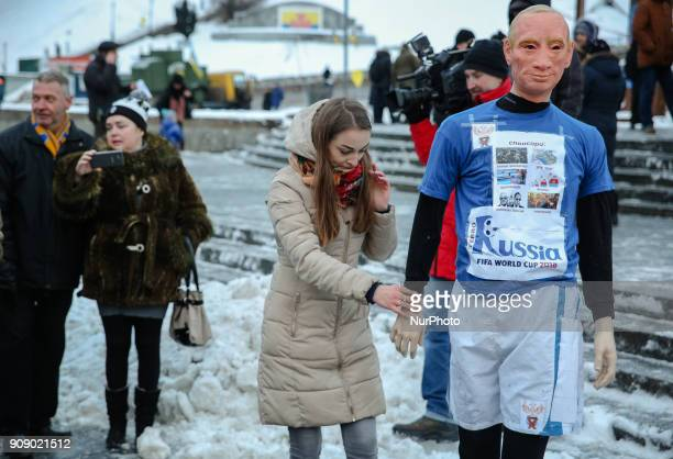 A girl adjusts a mannequin depicting Russian President Vladimir Putin dressed in a football uniform during the quotStop Putin Stop warquot rally and...