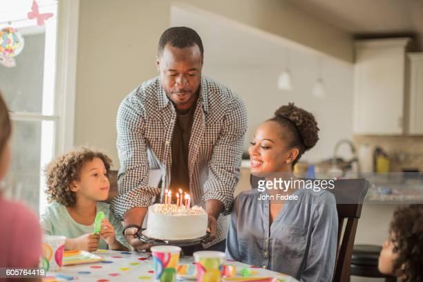 Girl admiring birthday cake at party
