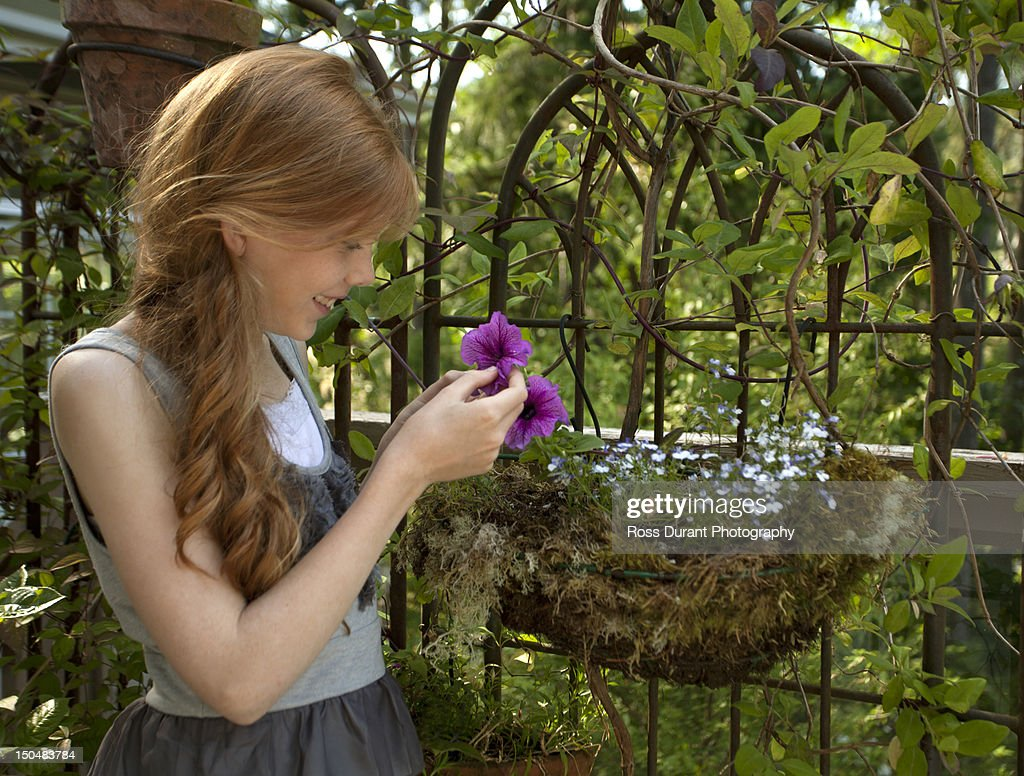 Girl Admiring Flowers In A Garden Stock Photo | Getty Images