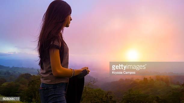Girl Admiring Sunset over Mountain Landscape