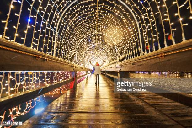 girl admiring the tunnel with holiday lights, public lighting for the christmas and new year holidays - romania stock pictures, royalty-free photos & images