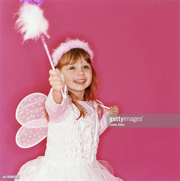 Girl Against a Pink Background Smiling and Holding a Wand