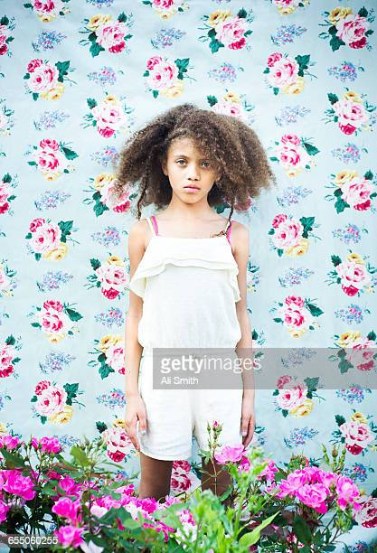 Girl against floral wall