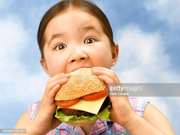 Girl (6-7) against sky, eating large hamburger, close-up, portrait