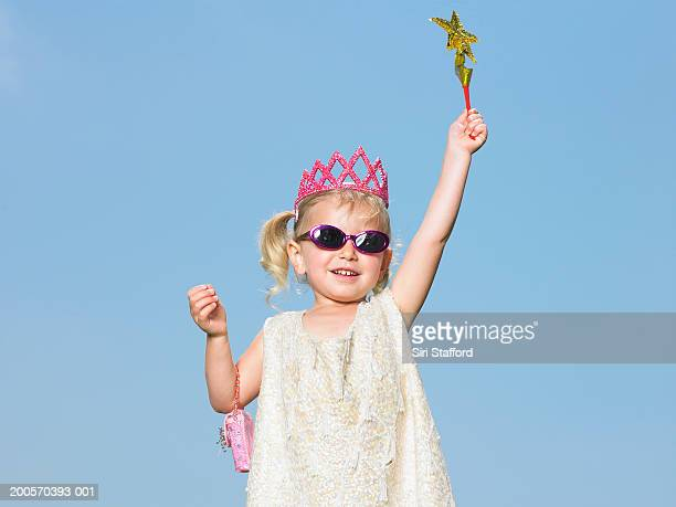 Girl (3-4) against sky, wearing crown and holding up magic wand