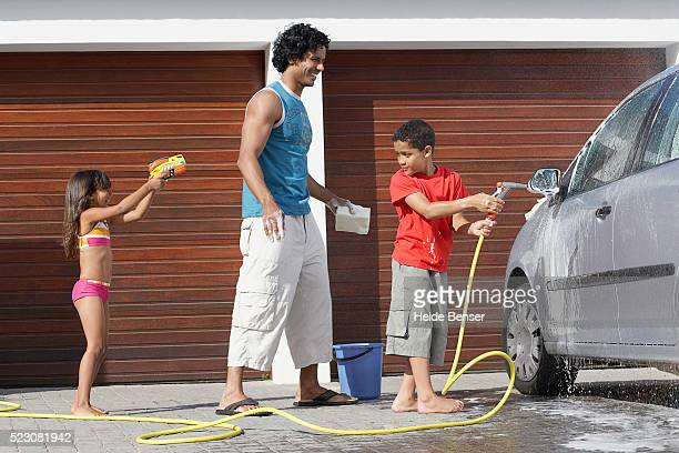 Girl aiming water gun at father and brother