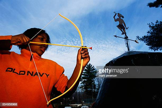 A girl aims a toy bow and arrow at the Pinegrove Dude Ranch Resort The vacation destination is located in New York's Catskill Mountains | Location...
