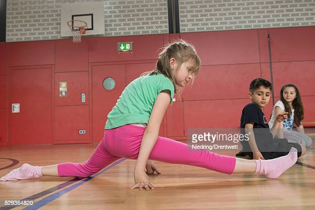 girl amazed others by splitting her legs in sports hall, munich, bavaria, germany - kurdish girl stock photos and pictures