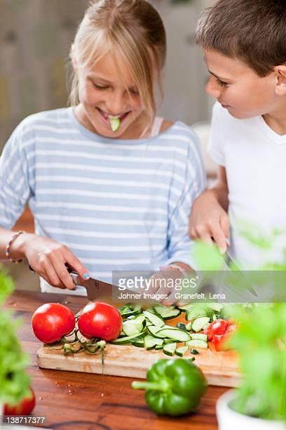 a girl and a boy cutting vegetables - alleen kinderen stockfoto's en -beelden