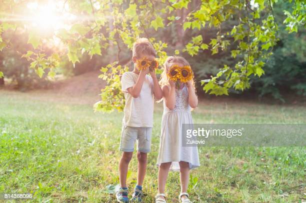 Girl and a boy playing around with flowers